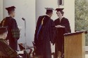 Preview image of Female Graduate receives her diploma from Dr. Kenneth Crispell