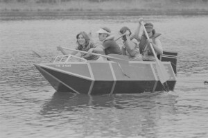 Architecture students paddling cardboard boat