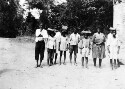 """Preview image of Rural school children of original American stock in Liberia. Each larger child had a smaller one to carry his books which was done in the manner shown. Whether this was just a brother and sister act or an indication of the """"domestic"""" slavery still common thru out Africa we could not determine."""