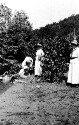 Preview image of Two unidentified women, one man, and a little girl near a stream.